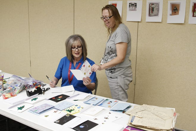Mary Zickefoose, right, shows Shannon Farrell a Christmas card she made for a local retirement home Thursday at the at the San Juan Center for Independence in Farmington.
