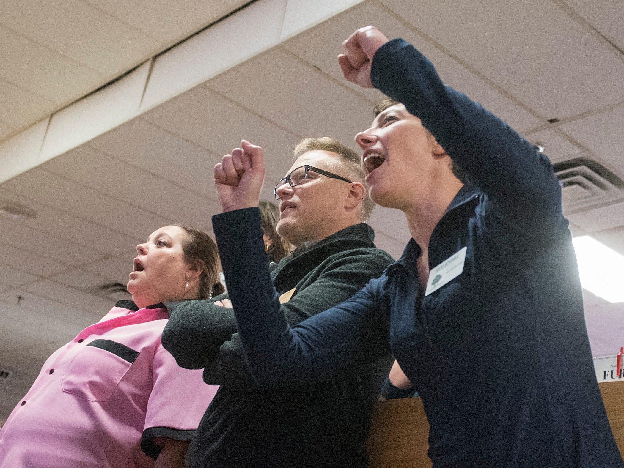 Theresa Rich, Steve Schneemann and Sara Bowman react to the falling pins.