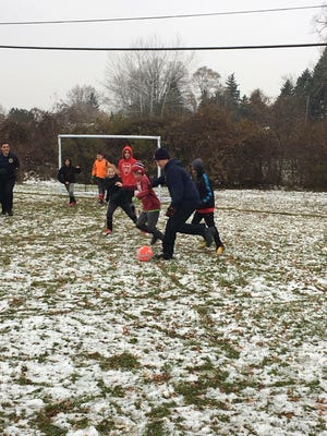 Westland Firefighters take on some local youngster in a chilly soccer game.