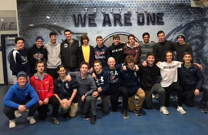 South Lyon Unified hockey team members pose in front of their new mural inside the Kensington Valley Ice House.