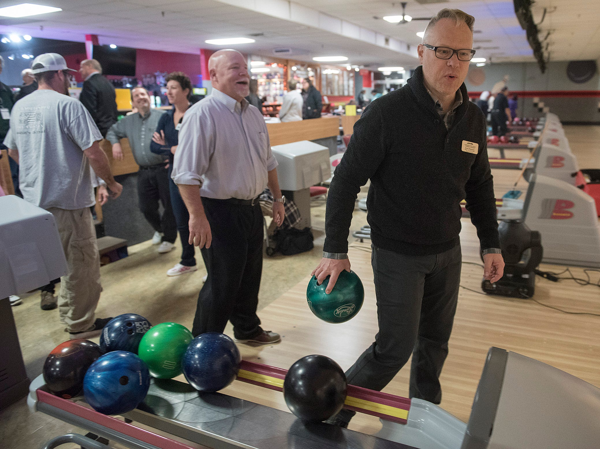 Farmington Mayor Steve Schneemann chooses his bowling ball and heads for his lane. Farmington Hills Mayor Ken Massey is right behind him.
