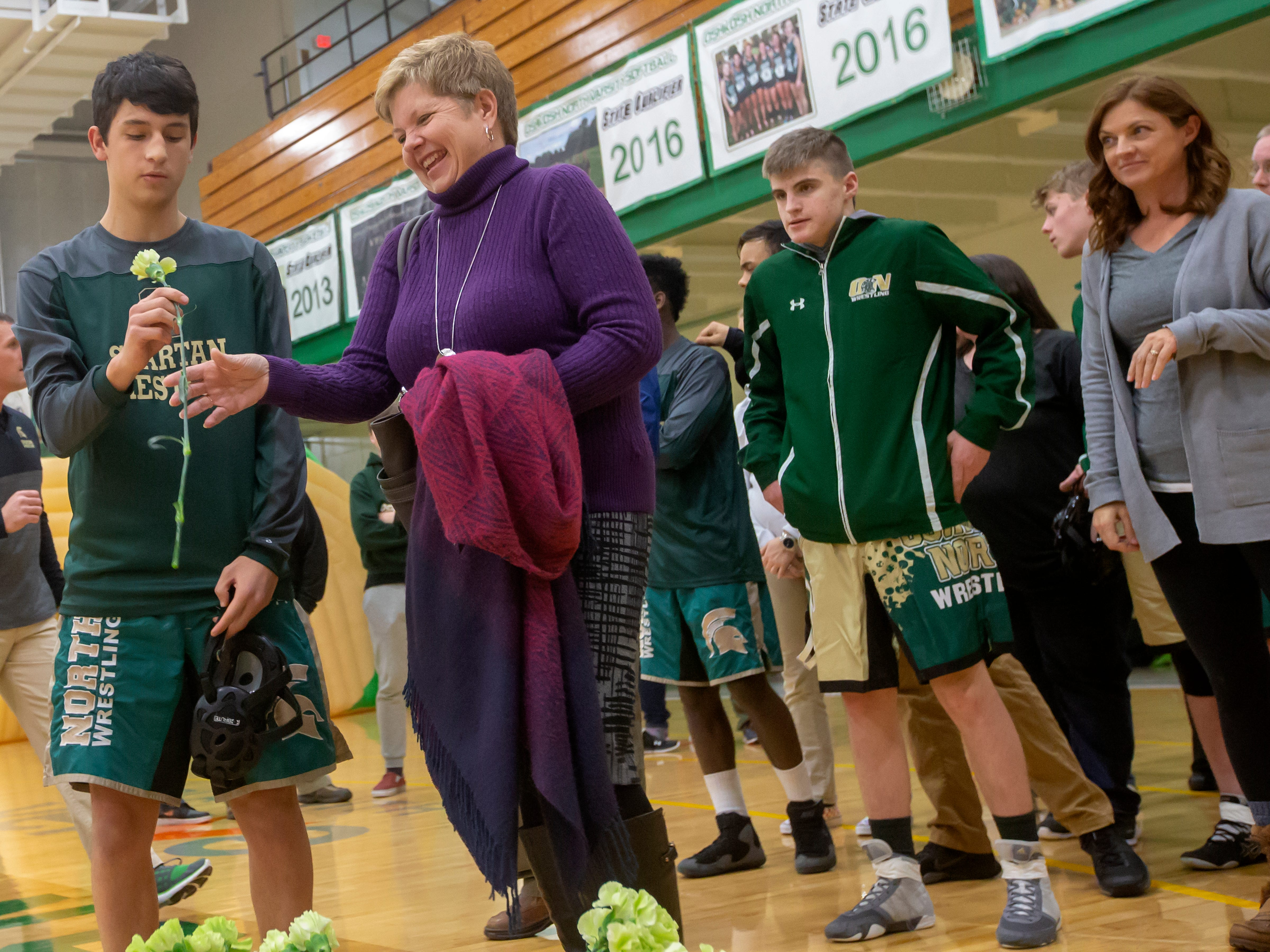 Oshkosh North's Jose Collins gives mom, Theresa Collins, a flower honoring parents during the Oshkosh North wrestling meet at the high school on Thursday, November 29, 2018.