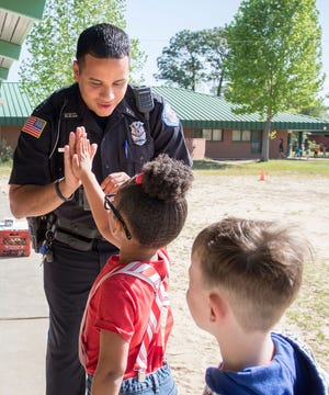 Michael Garcia, an off-duty Pensacola police officer and school resource officer, high-fives students April 18, 2018, while walking around Scenic Heights Elementary School in Pensacola.