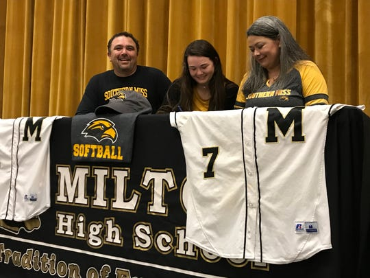 Milton shortstop Maddie Vasquez (center) is joined by her father  Quinn (left) and mother Rachel (right) in signing with Southern Miss in a ceremony at Milton High on Nov. 30, 2018.