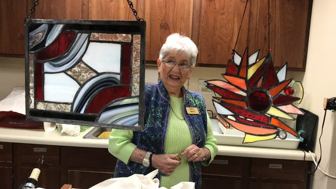 Azalea Trace resident Dotty Kass shows off some of the stained glass pieces she has created.