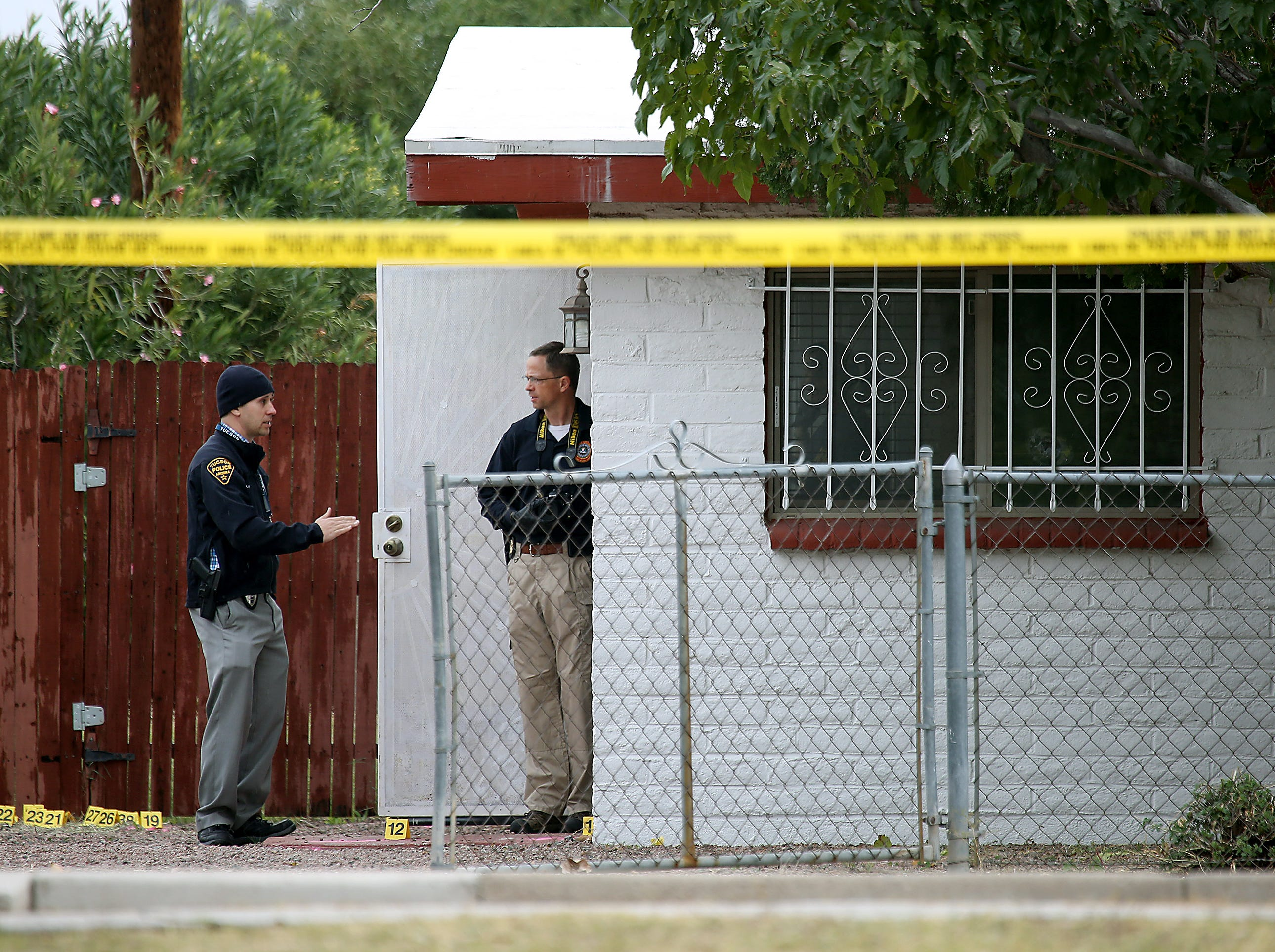 A Tucson Police Department investigator (left) talks with another law-enforcement officer Nov. 30, 2018, at the scene where Deputy U.S. Marshal Chase White was serving a felony arrest warrant when he was shot and killed Nov. 29 outside a north Tucson house.