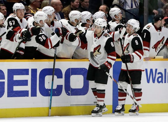 Arizona Coyotes center Nick Schmaltz (8) is congratulated after scoring a goal against the Nashville Predators in the second period of an NHL hockey game Thursday, Nov. 29, 2018, in Nashville, Tenn. (AP Photo/Mark Humphrey)