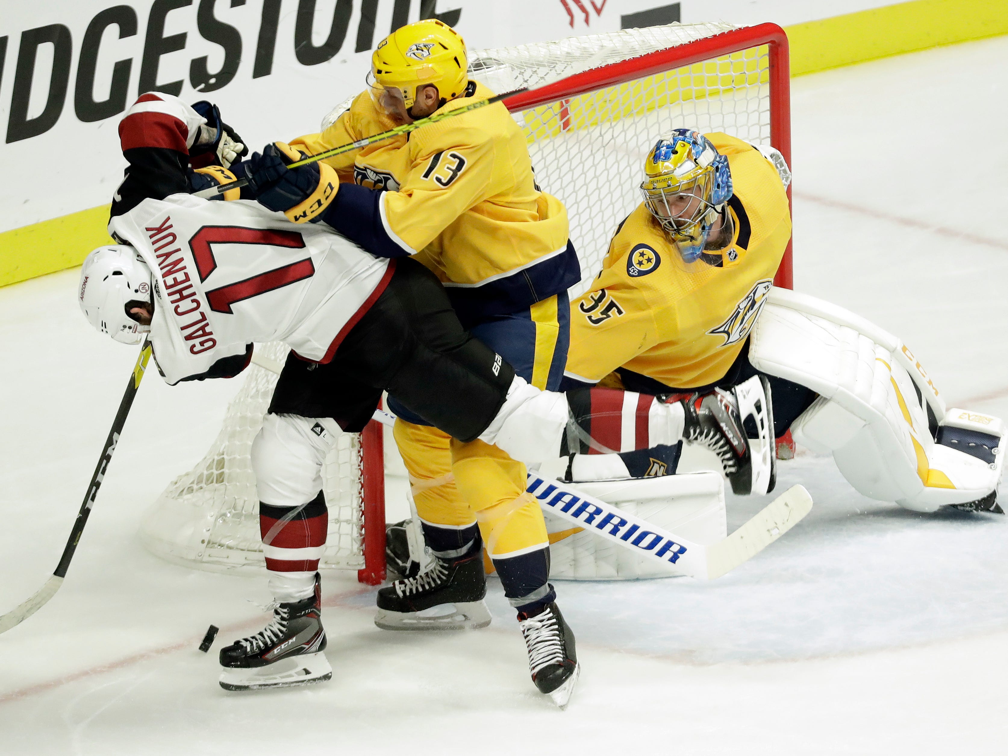 Arizona Coyotes center Alex Galchenyuk (17) is checked by Nashville Predators center Nick Bonino (13) as goaltender Pekka Rinne (35), of Finland, guards the net in the third period of an NHL hockey game Thursday, Nov. 29, 2018, in Nashville, Tenn. (AP Photo/Mark Humphrey)