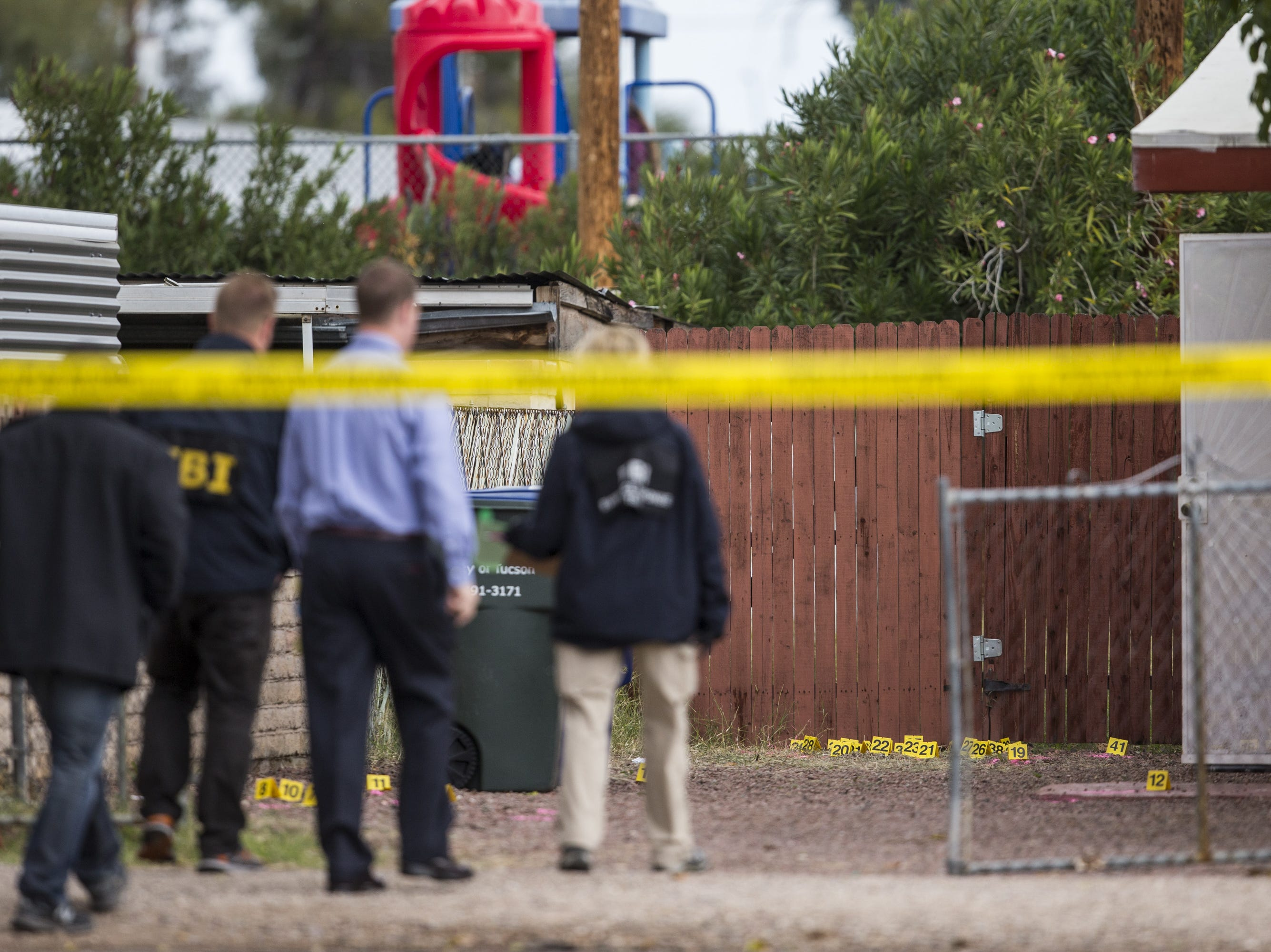 Evidence markers are seen on the ground as law enforcement investigates the scene of a fatal shooting of a deputy U.S. marshal on Friday, Nov. 30, 2018, in Tucson, Ariz. Law enforcement said Deputy U.S. Marshal Chase White was fatally shot by a suspect, Ryan Schlesinger, 26, while he was serving a fugitive warrant at a house on Thursday.