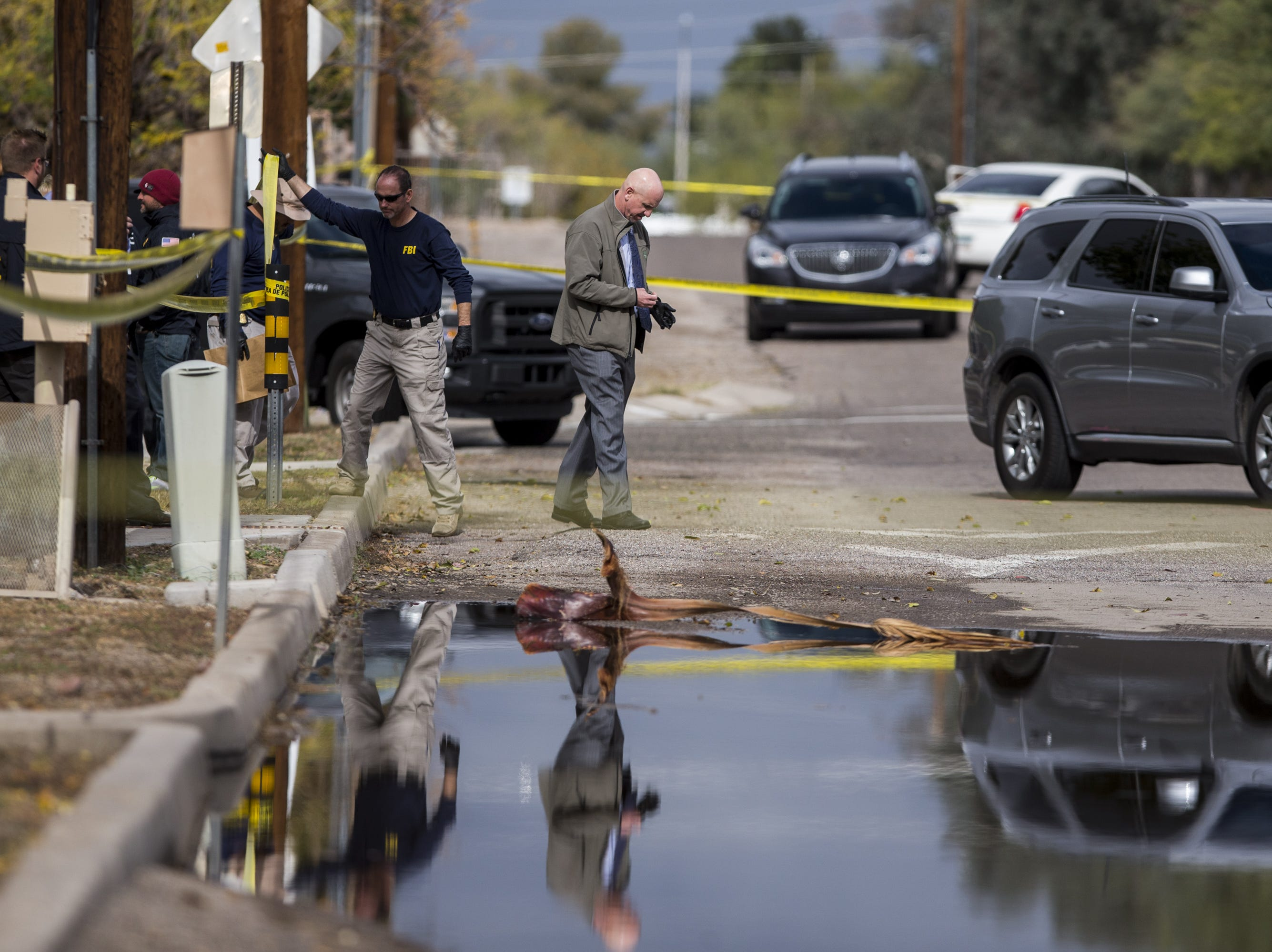 Law enforcement investigates the scene of a fatal shooting of a deputy U.S. marshal on Friday, Nov. 30, 2018, in Tucson, Ariz. Law enforcement said Deputy U.S. Marshal Chase White was fatally shot by a suspect, Ryan Schlesinger, 26, while he was serving a fugitive warrant at a house on Thursday.