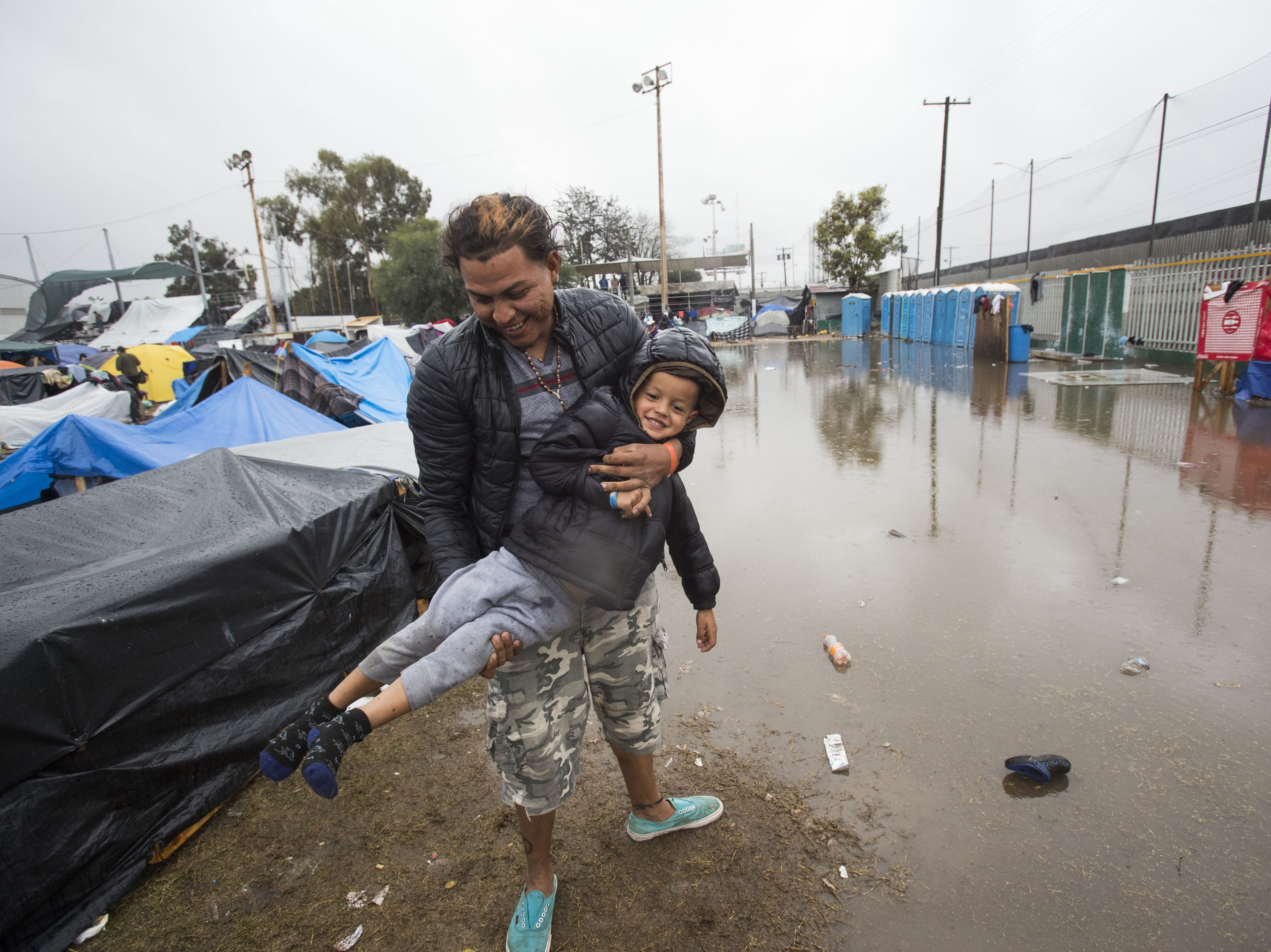 A father and his son enjoy a light moment as dirty water ponds near their tent at the shelter.