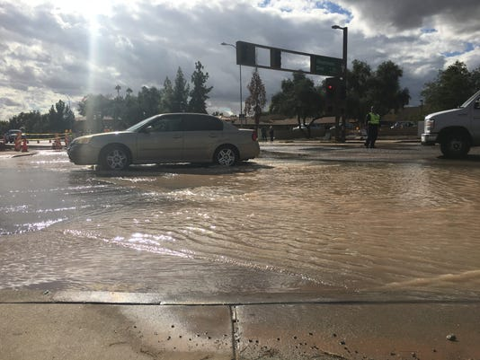 Cars drive through water after pipe burst