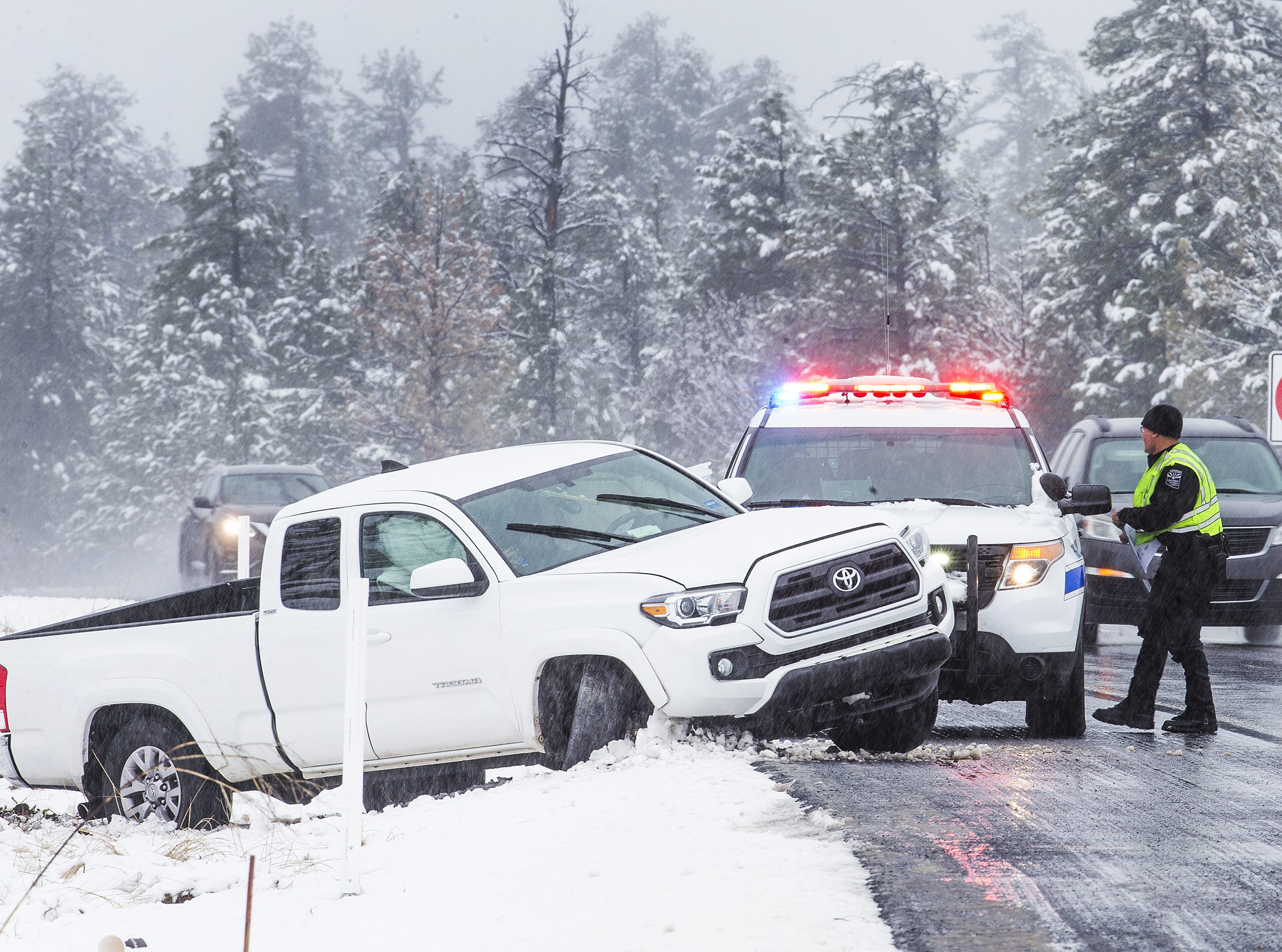 A pickup slid off of the northbound lanes of I-17, 1 mile north of Fox Ranch Road, south of Flagstaff on November 30, 2018. A Department of Public Safety trooper prepares to lay down traffic cones to alert other drivers. Snow has fallen in northern Arizona causing dangerous driving conditions that have resulted in cars and trucks sliding off the road.