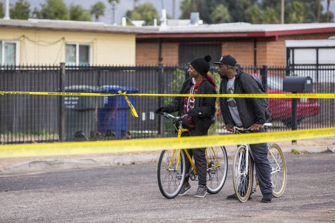 Bystanders watch as law enforcement investigates the scene of a fatal shooting of a deputy U.S. marshal on Friday, Nov. 30, 2018, in Tucson, Ariz. Law enforcement said Deputy U.S. Marshal Chase White was fatally shot by a suspect, Ryan Schlesinger, 26, while he was serving a fugitive warrant at a house on Thursday.