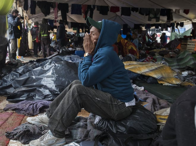The Benito Juarez sports complex, which is serving as a shelter for over 6,000 caravan migrants, was drenched with heavy rains, causing already precarious living conditions to worsen at the shelter in Tijuana, Mexico, on Nov. 29, 2018. A man from El Salvador contemplates his situation.