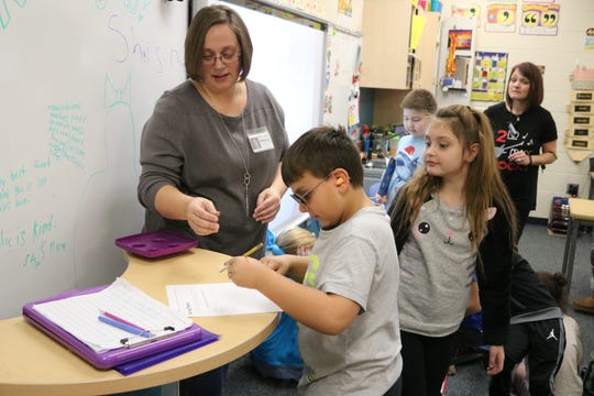 Braylen LoPresto, a second grade student at Bataan Primary, tries to write with darkened sun glasses and other simulated impairments to understand the difficulties that many elderly face.