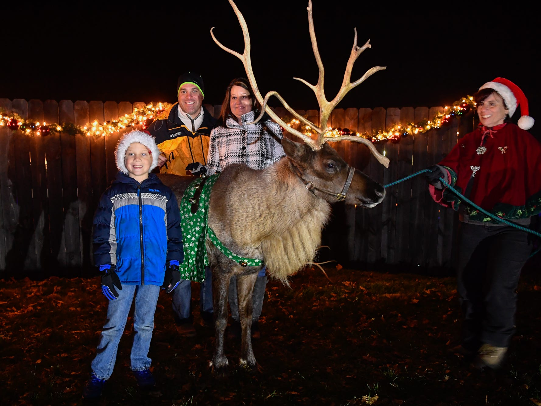 Cameron Auchey, 8, and his parents Mitchell and Jaime, of Spring Grove, pose with Aspen the reindeer during the 3rd annual Christmas tree lighting in Spring Grove, Thursday, November 29, 2018. 