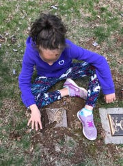 Brittany Winters sits over the grave of her twin, Alyssa, who passed away from cardiac defects a month after her birth.