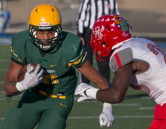 Bishop Manogue Miners  Peyton Dixon (10) runs by the attempted tackle by Arbor View Aggies Darius Harrison (23) in the second half of their NIAA 4A State Semifinal football game at McQueen on Saturday, Nov. 24.