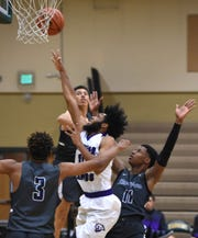 Spanish Springs' Dante Craig goes up to shoot between Birminghan High's Tyrese Windham, left, and Corey Cofield II in the first game of the 2018 Wild West Shoot Out at Bishop Manogue High School on Thursday.