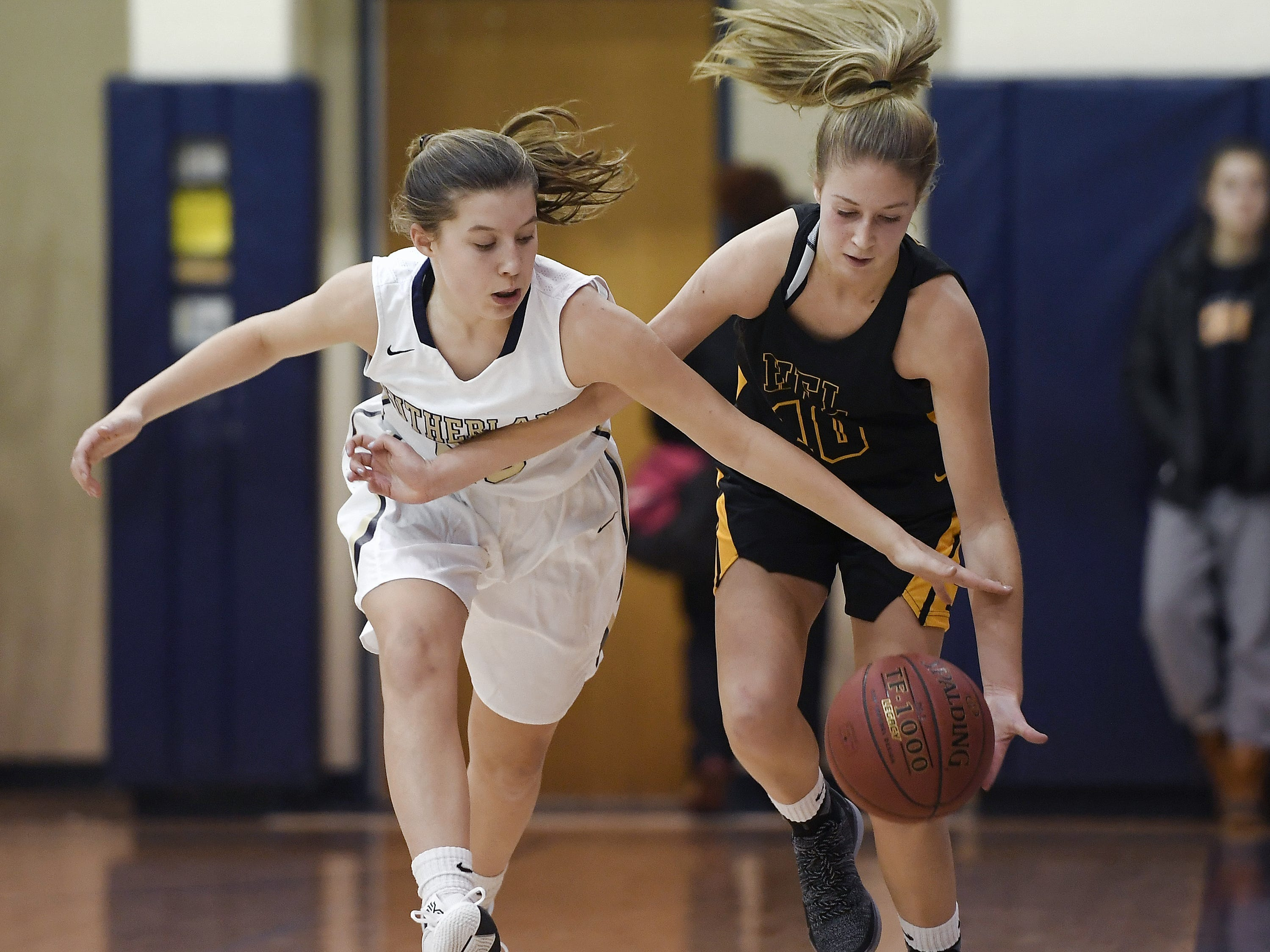 Pittsford Sutherland's Ellie Bergin, left, and HF-L's Hannah Selke chase a loose ball during a regular season game played at Pittsford Sutherland High School on Thursday, Nov. 29, 2018. Pittsford Sutherland beat Honeoye Falls-Lima in overtime 53-47.