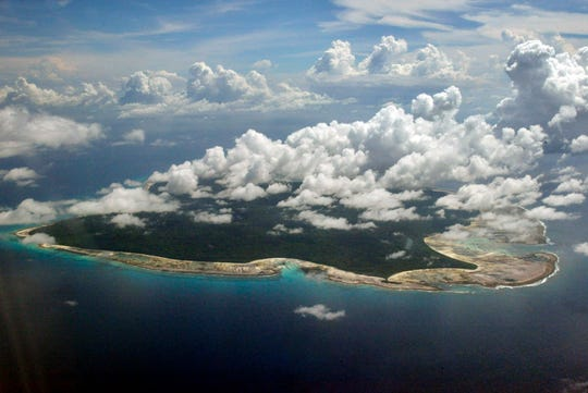 In this Nov. 14, 2005 file photo, clouds hang over the North Sentinel Island, in India's southeastern Andaman and Nicobar Islands. A rights group that works to protect tribal people has urged Indian authorities to abandon efforts to recover the body of an American man who was thought to be killed by inhabitants of an island where outsiders are effectively forbidden by Indian law.