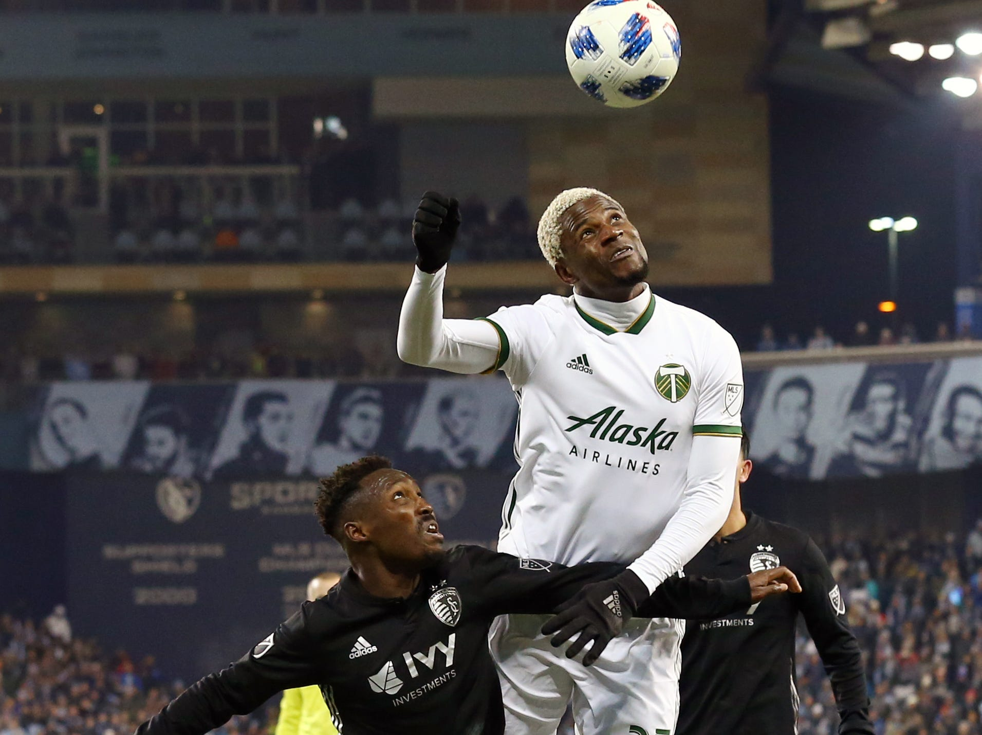 Nov 29, 2018; Kansas City, KS, USA; Portland Timbers forward Dairon Asprilla (27) heads the ball over Sporting Kansas City forward Gerso (12) during the second half in the second leg of the MLS Western Conference Championship at Children's Mercy Park. Mandatory Credit: Jay Biggerstaff-USA TODAY Sports