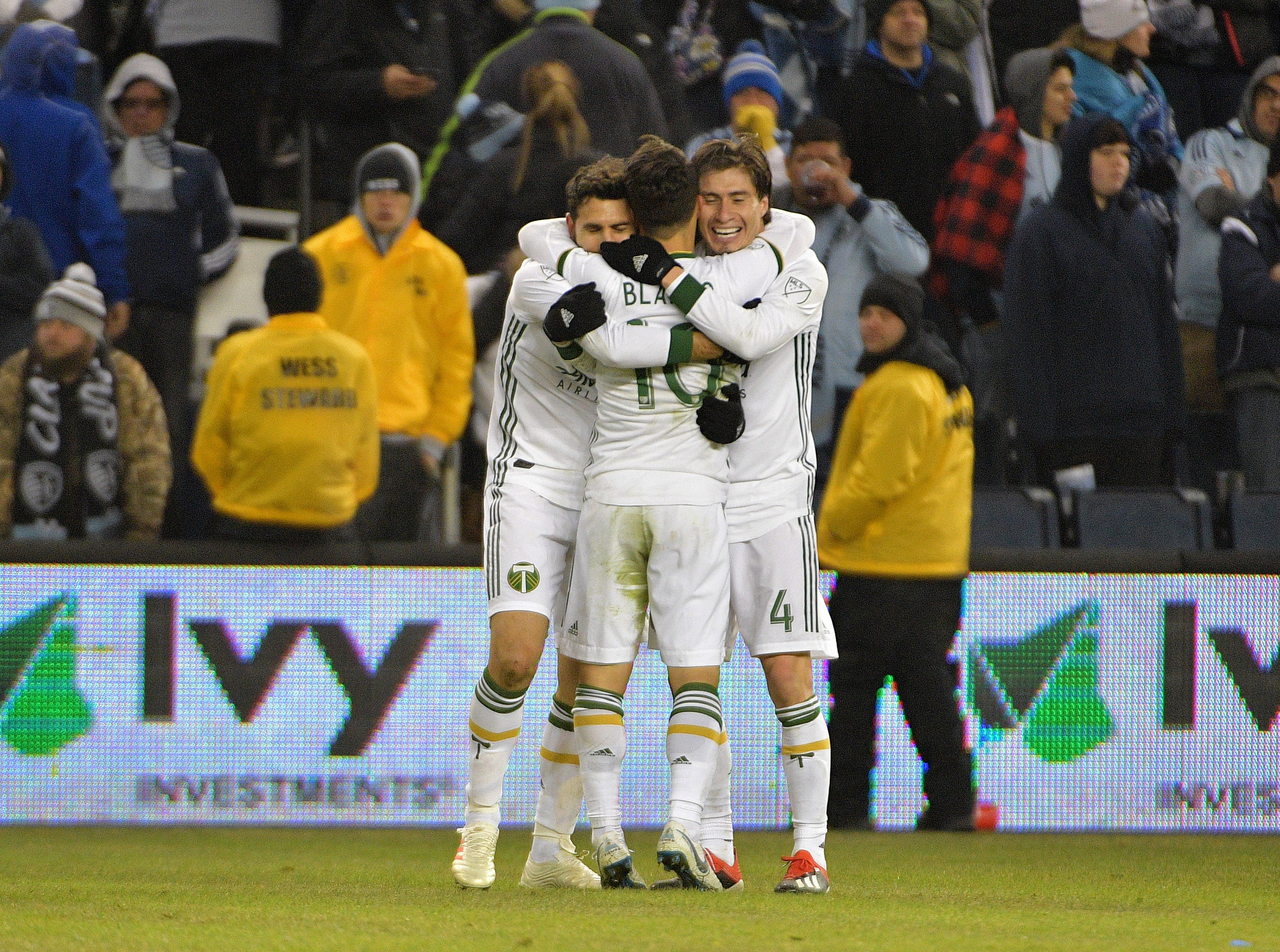 Nov 29, 2018; Kansas City, KS, USA; Portland Timbers midfielder Diego Valeri (8) celebrates with defender Jorge Villafana (4) and midfielder Sebastian Blanco (10) after scoring a goal  against Sporting Kansas City in the second leg of the MLS Western Conference Championship at Children's Mercy Park. Mandatory Credit: Denny Medley-USA TODAY Sports