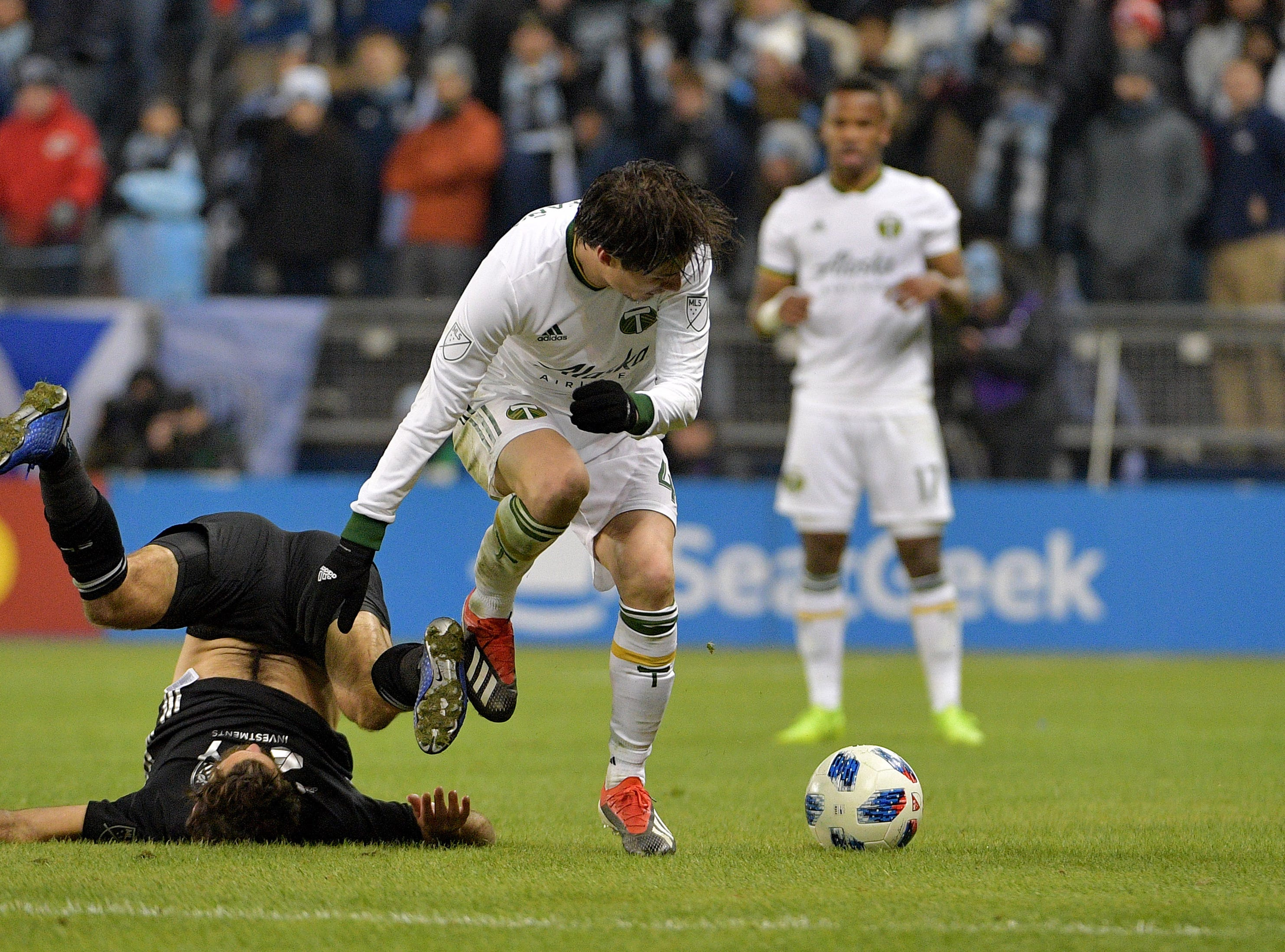 Nov 29, 2018; Kansas City, KS, USA; Sporting Kansas City midfielder Graham Zusi (8) and Portland Timbers defender Jorge Villafana (4) fight for the ball in the second leg of the MLS Western Conference Championship at Children's Mercy Park. Mandatory Credit: Denny Medley-USA TODAY Sports