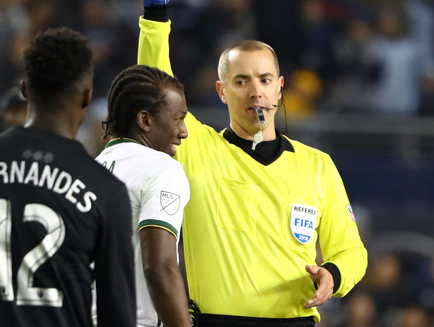 Nov 29, 2018; Kansas City, KS, USA; Portland Timbers midfielder Diego Chara (21) receives a yellow card from referee Mark Geiger during the second half against the Sporting Kansas City in the second leg of the MLS Western Conference Championship at Children's Mercy Park. Mandatory Credit: Jay Biggerstaff-USA TODAY Sports