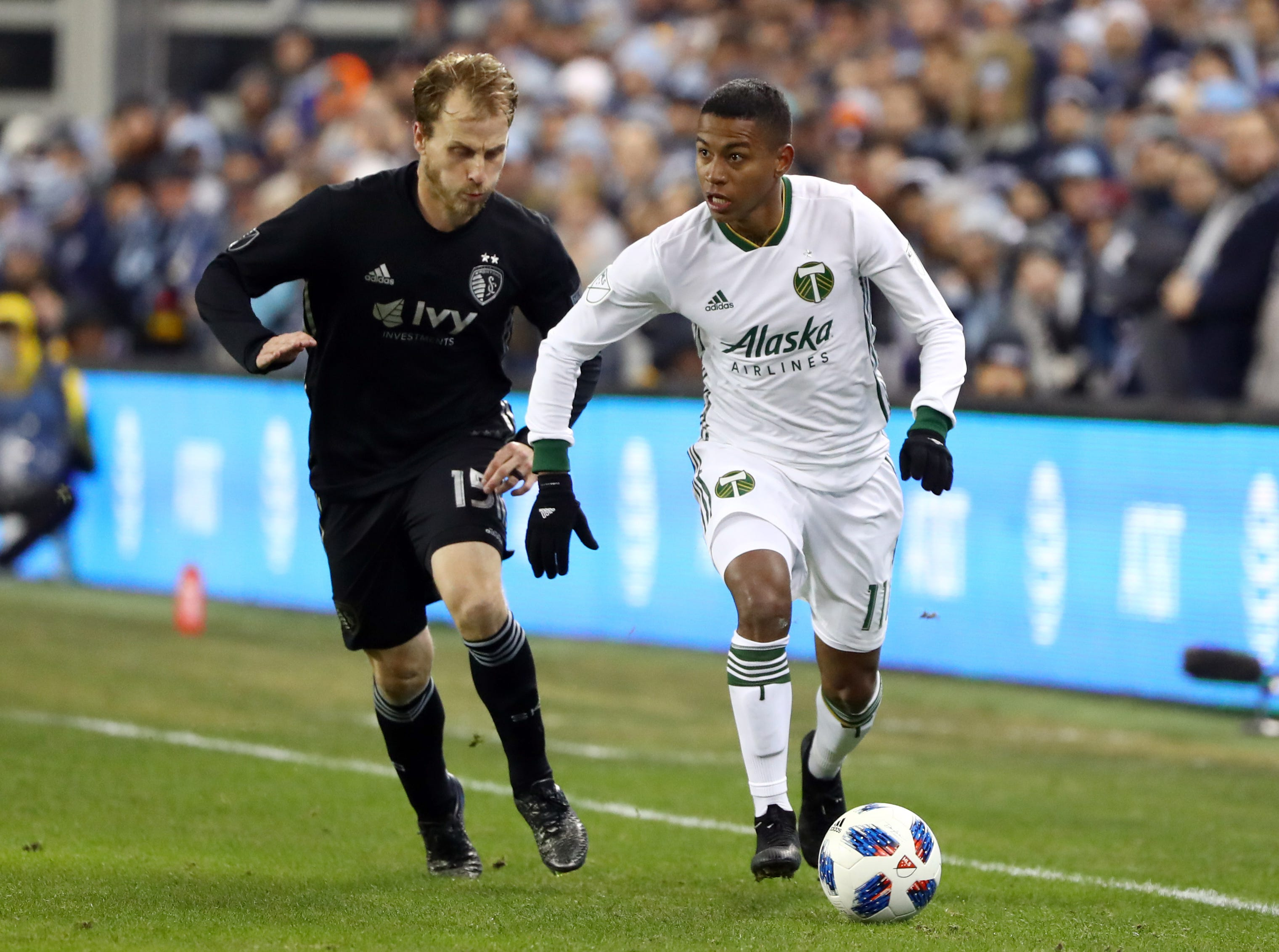 Nov 29, 2018; Kansas City, KS, USA; Portland Timbers forward Andy Polo (11) dribbles the ball against Sporting Kansas City defender Seth Sinovic (15) during the second half in the second leg of the MLS Western Conference Championship at Children's Mercy Park. Mandatory Credit: Jay Biggerstaff-USA TODAY Sports