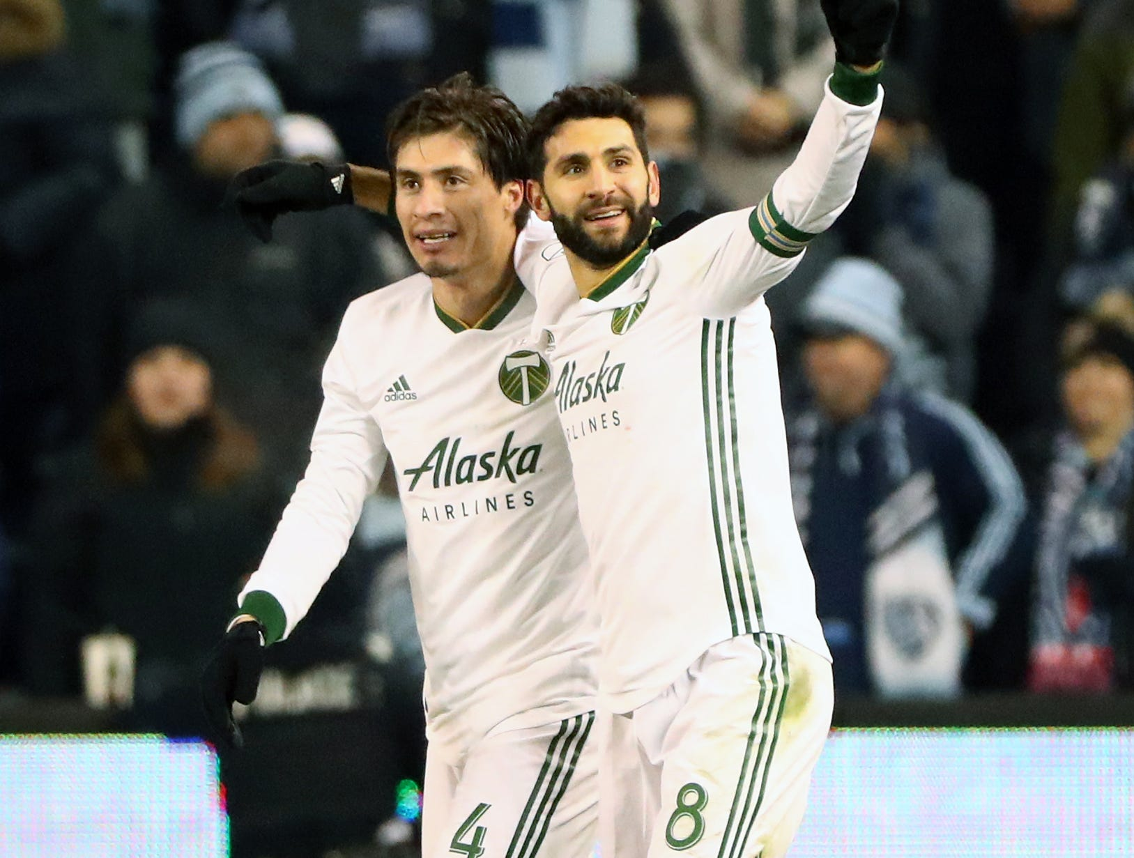 Nov 29, 2018; Kansas City, KS, USA; Portland Timbers midfielder Diego Valeri (8) celebrates with defender Jorge Villafana (4) after scoring a goal against the Sporting Kansas City during the second half in the second leg of the MLS Western Conference Championship at Children's Mercy Park. Mandatory Credit: Jay Biggerstaff-USA TODAY Sports