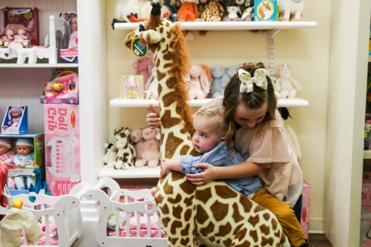 Madison Myers, 9, holds her brother, Grayson, 2, up on a giraffe Nov. 29, 2018, at Fancy Pants Children's Boutique in San Angelo.