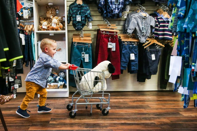 Grayson, 2, pushes a cart through the store Nov. 29, 2018, at Fancy Pants Children's Boutique in San Angelo.