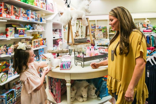 Hailey Myers, owner, talks to her daughter, Madison, 9, as she points out a wall she likes Nov. 29, 2018, at Fancy Pants Children's Boutique in San Angelo.