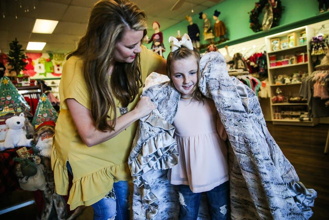 Hailey Myers, owner, puts a Cuddle Couture blanket on her daughter, Madison, 9, Nov. 29, 2018, at Fancy Pants Children's Boutique in San Angelo.