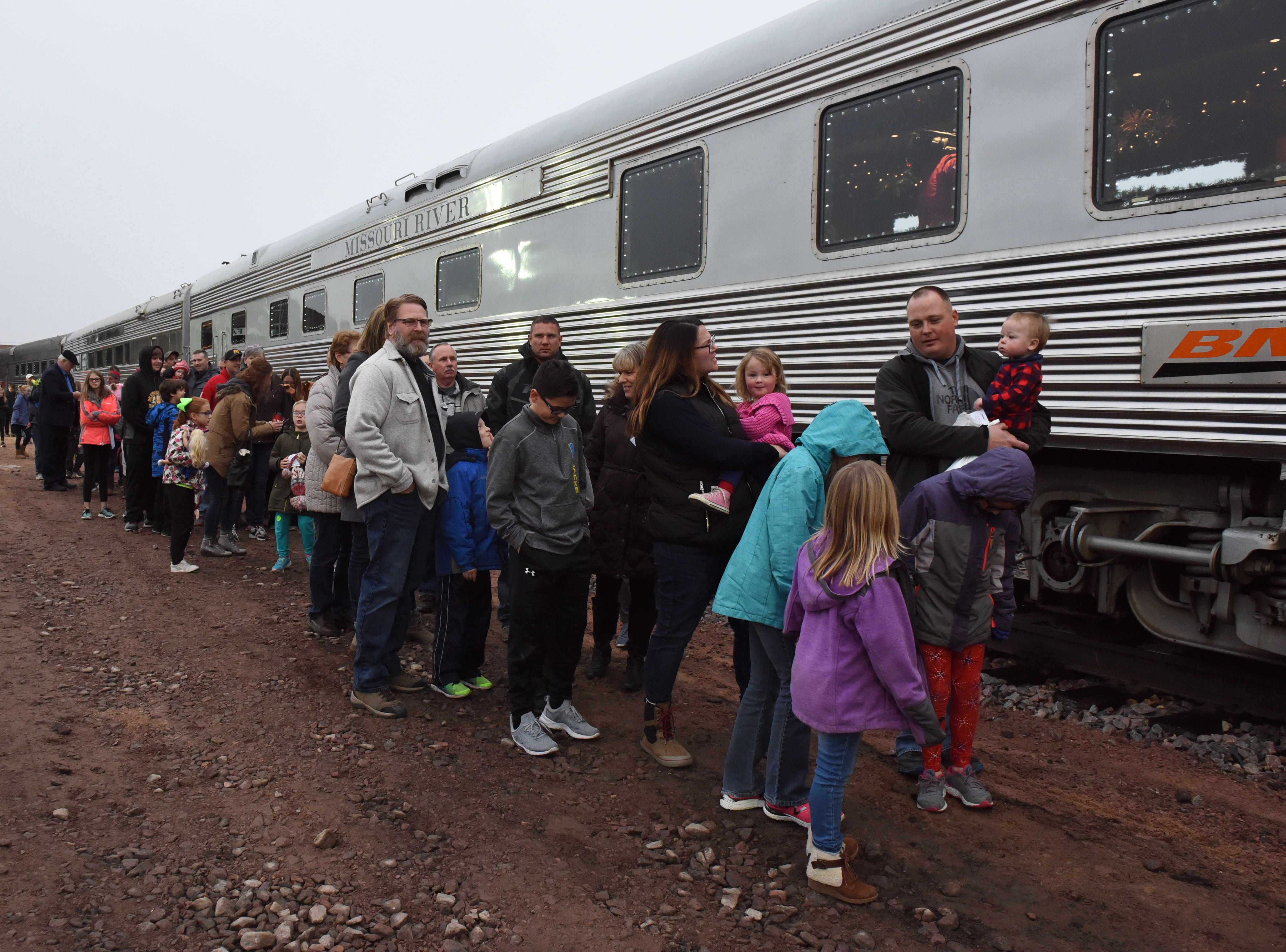 People board the BNSF train in Sioux Falls, S.D., Thursday, Nov. 29, 2018.
