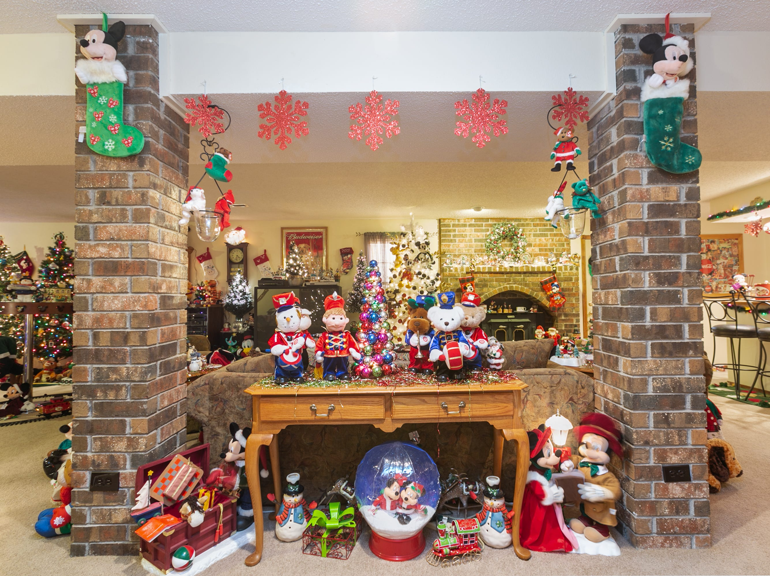 The lower living area is filled with holiday joy, from Mickey and Minnie carolers to train sets.