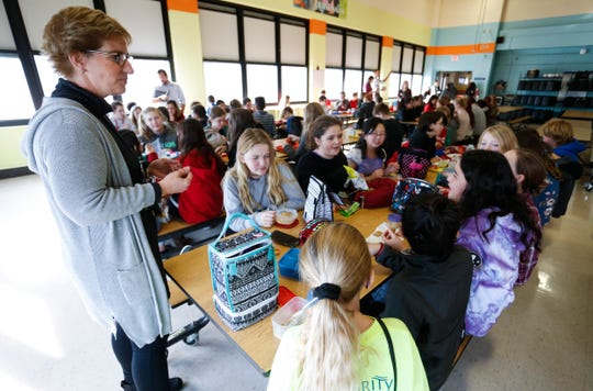 Reed Academy Principal Debbie Grega talks with students during lunch on Thursday, Nov 29, 2018. Grega is retiring after 12 years leading the school.