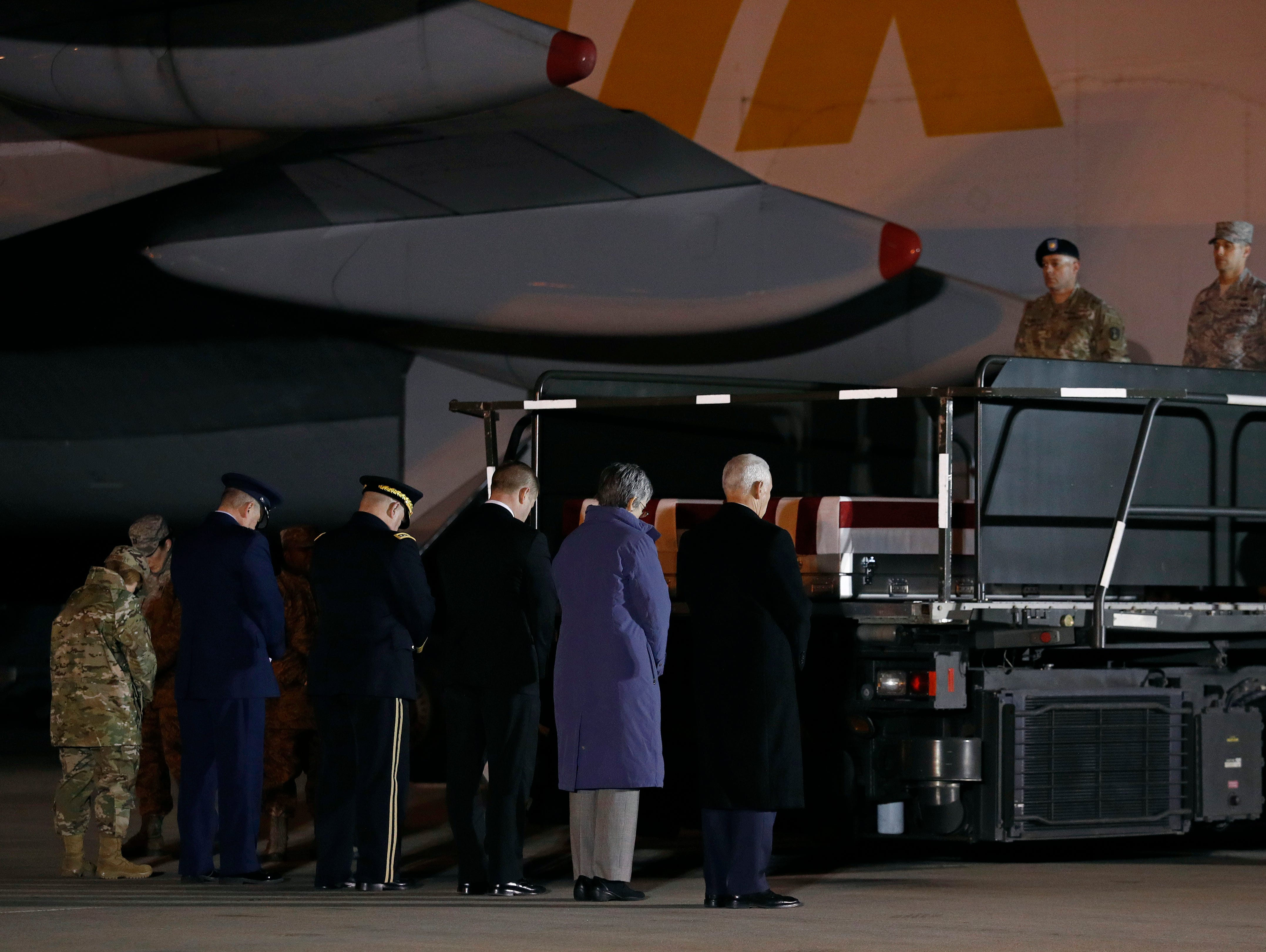 Vice President Mike Pence, right, pauses in prayer with members of an official party in front of transfer cases containing the remains of U.S. Army Capt. Andrew P. Ross and U.S. Air Force Staff Sgt. Dylan J. Elchin, Friday, Nov. 30, 2018, at Dover Air Force Base, Del. According to the Department of Defense, Ross, 29, of Lexington, Va., and Elchin, 25, of Hookstown, Pa., were killed Nov. 27, 2018, by a roadside bomb in Andar, Ghazni Province, Afghanistan.