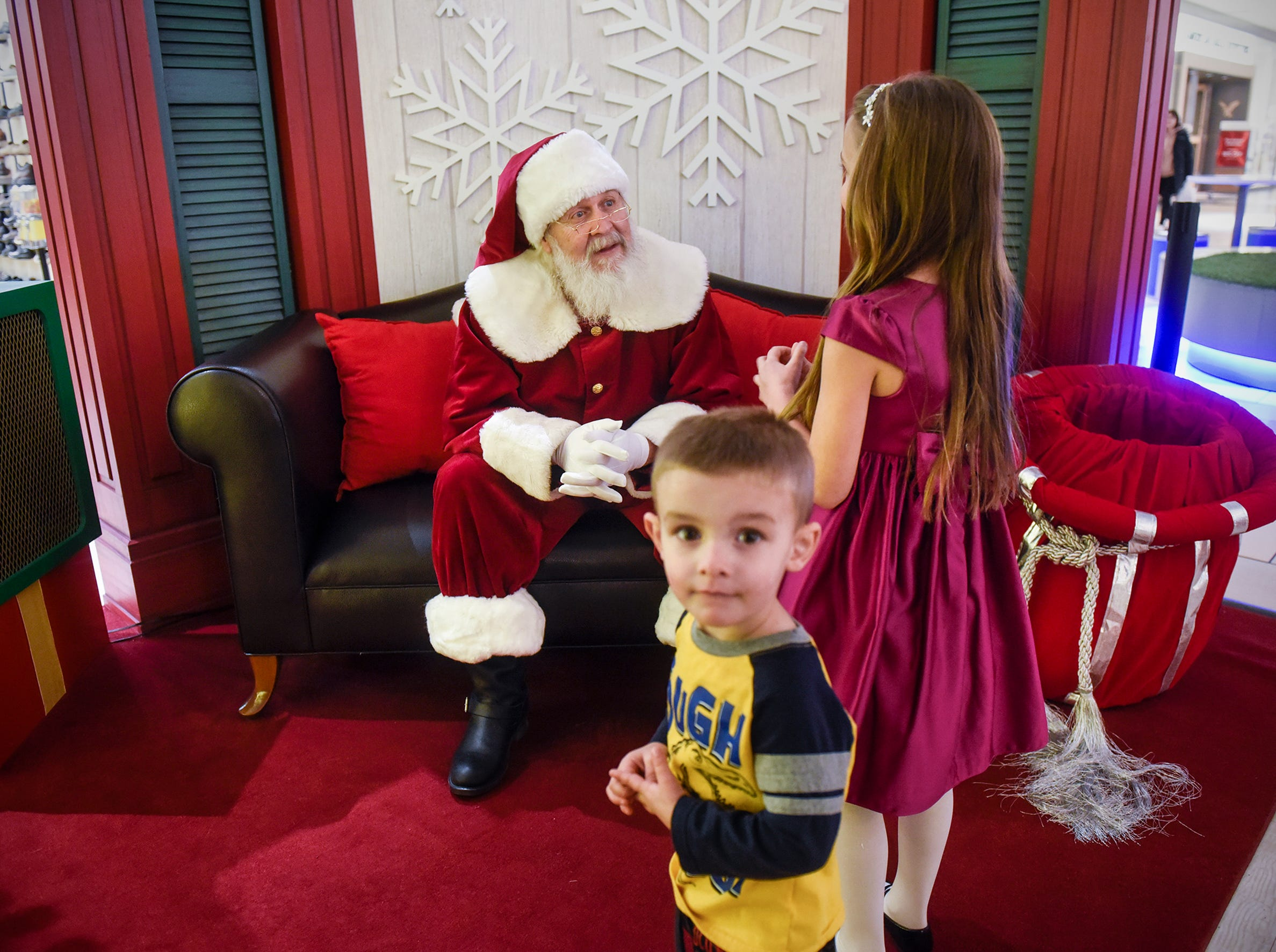 Theodore and Reese Janson get their turn to greet Santa Claus Thursday, Nov. 30, at Crossroads Center in St. Cloud.