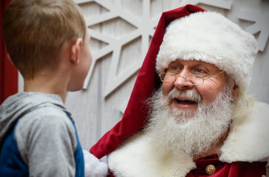 Santa Bob Hutton listens to a Christmas wish list Friday, Nov. 30, at Crossroads Center in St. Cloud.