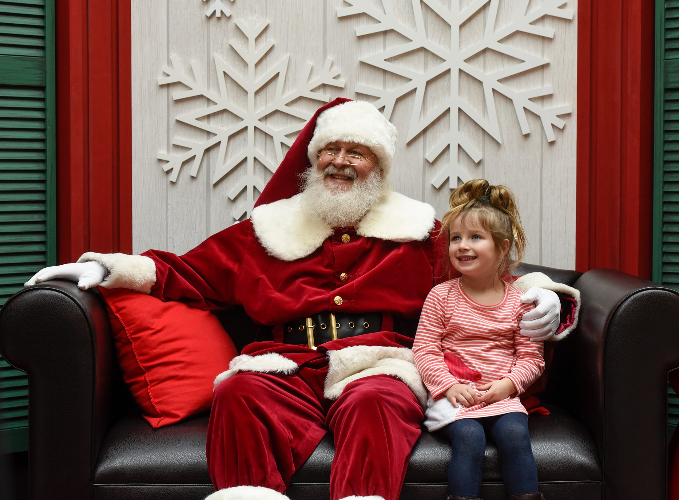 Brielle Asseln poses for a photograph with Santa Bob Hutton Friday, Nov. 30, at Crossroads Center in St. Cloud.