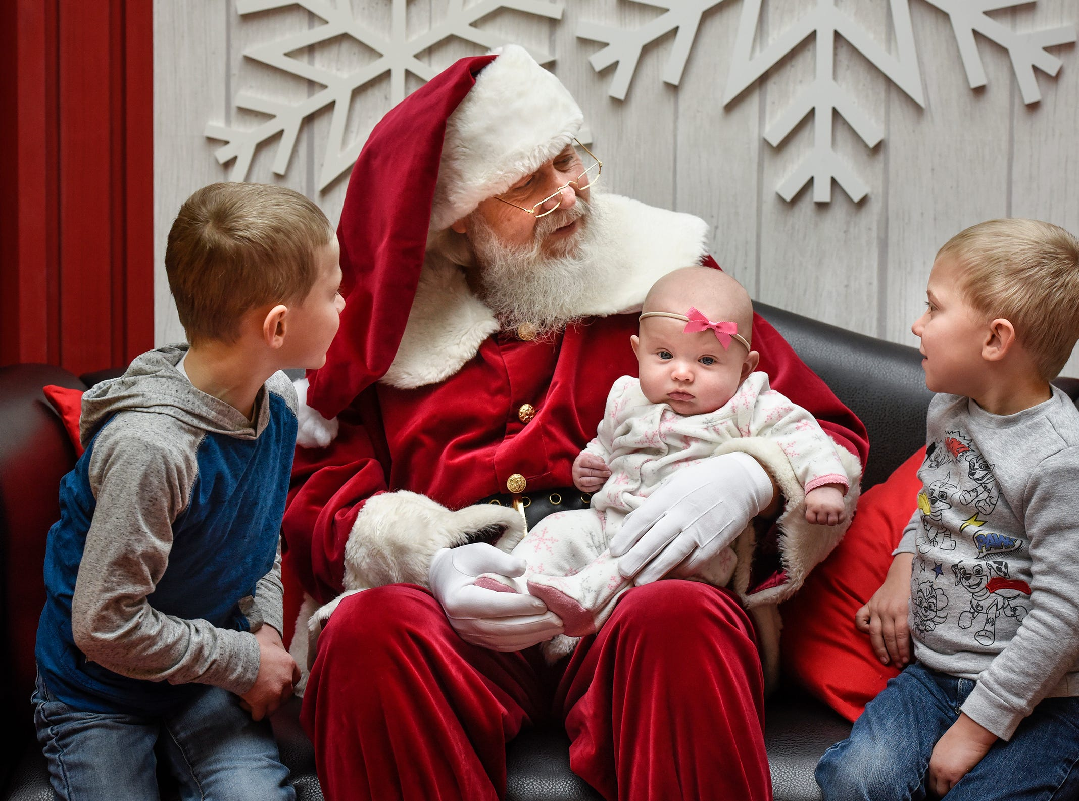 Wyatt, Connor and Delia Roelike talk with Santa Bob Hutton after sharing their Chirstmas wish lists and taking photographs Friday, Nov. 30, at Crossroads Center in St. Cloud.