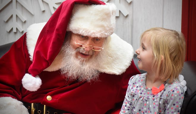 Santa Bob Hutton listens closely to Indy Grant's wish list Friday, Nov. 30, at Crossroads Center in St. Cloud.
