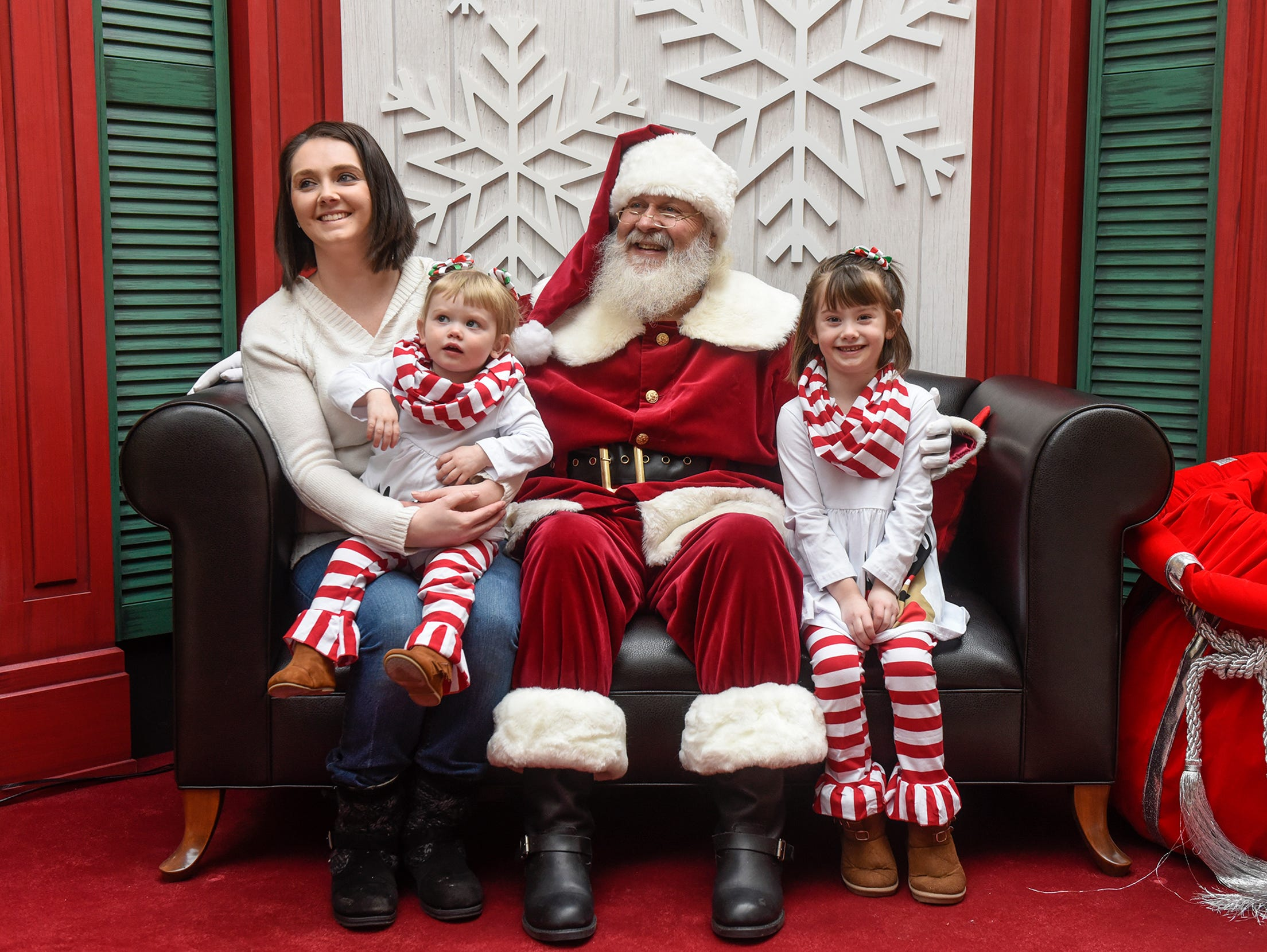 Madison and Rylee Shonyo pose with their mom Jessica and Santa Bob Hutton Friday, Nov. 30, at Crossroads Center in St. Cloud.