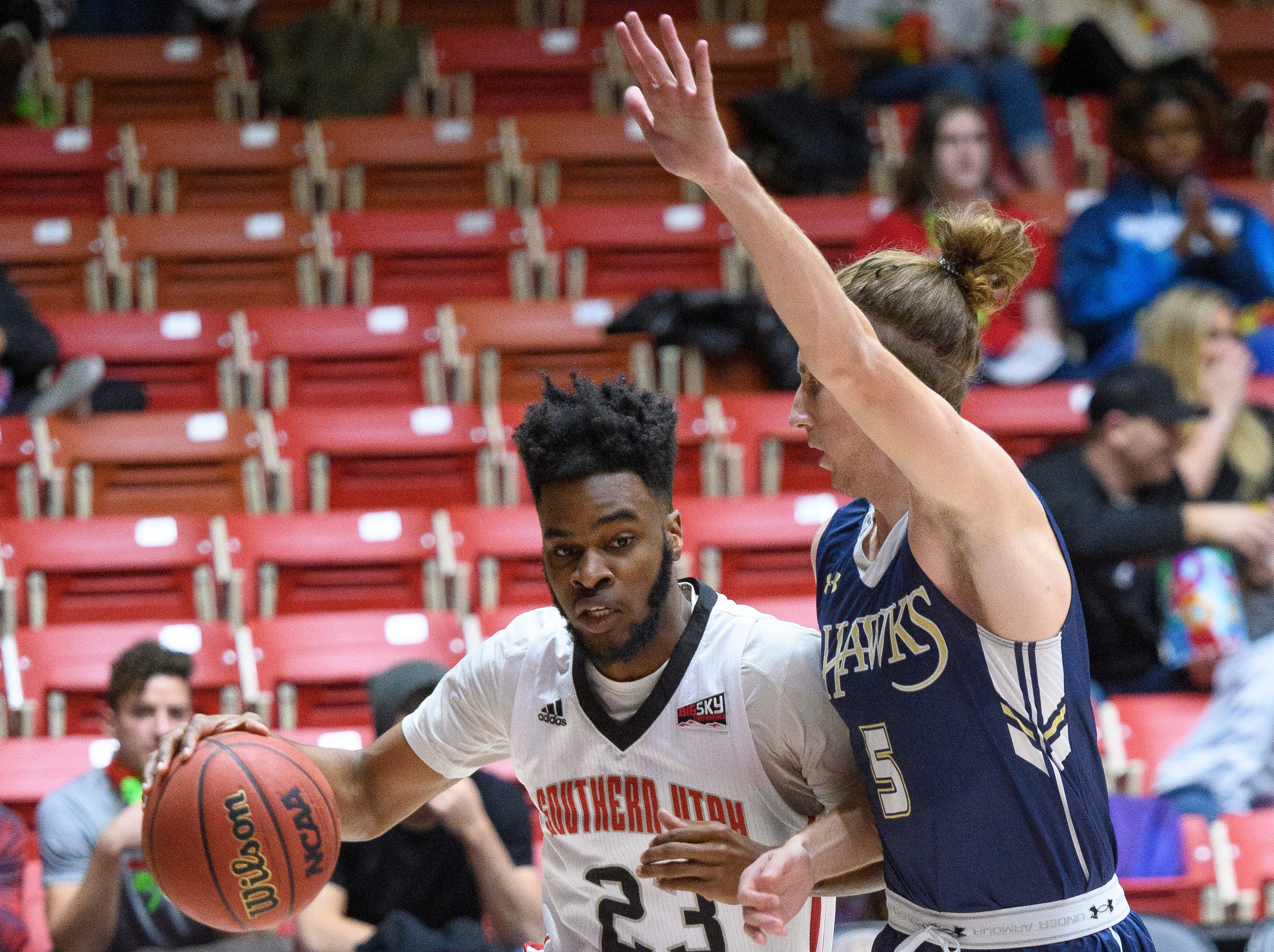 Southern Utah University junior Cameron Oluyitan (23) drives the ball into the key against San Diego Christian at the America First Event Center Thursday, November 29, 2018.