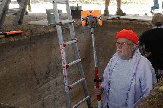 Crew chief Philip Gerrell measures the elevation above sea level of the pit during an archaeological dig being conducted by the Aucilla Research Institute at Wakulla Springs State Park Thursday, Nov. 29, 2018.