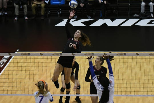 Florida State middle blocker Taryn Knuth (13) goes up to attack against the Florida Gators.