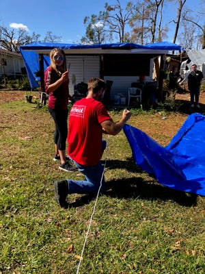 Mission 850 volunteers prepare a tarp for a roof-less home in Marianna following Hurricane Michael.
